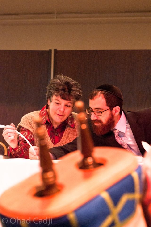 Congregant Fern Schwartz, of Mt. Lebanon, fills in a letter with Rabbi Selwyn. Schwartz is the co-chair of Beth El's bingo events, which raised money to fund the writing of the new Torah.